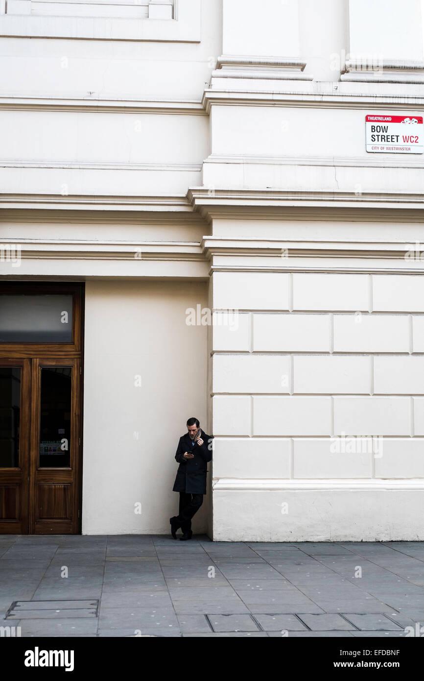 London UK smoker alone sidewalk - Stock Image