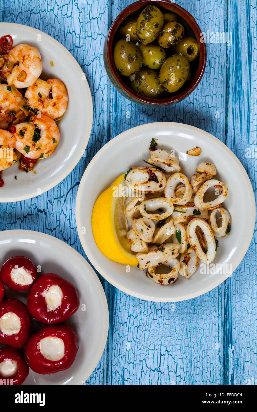 Tapas of squid, stuffed peppers, olives and prawns - Stock Image