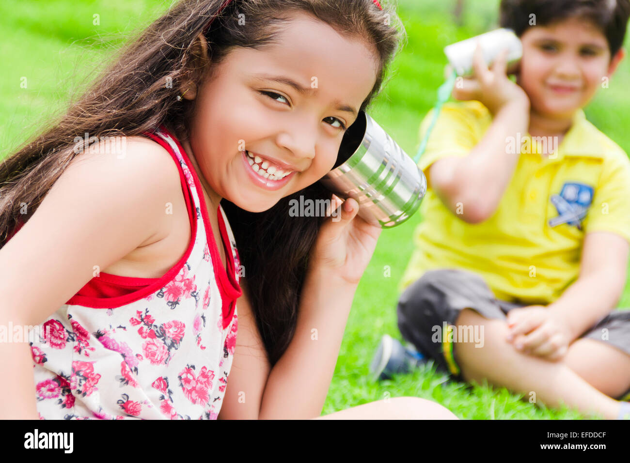 2 indian children friend park toy phone talking - Stock Image