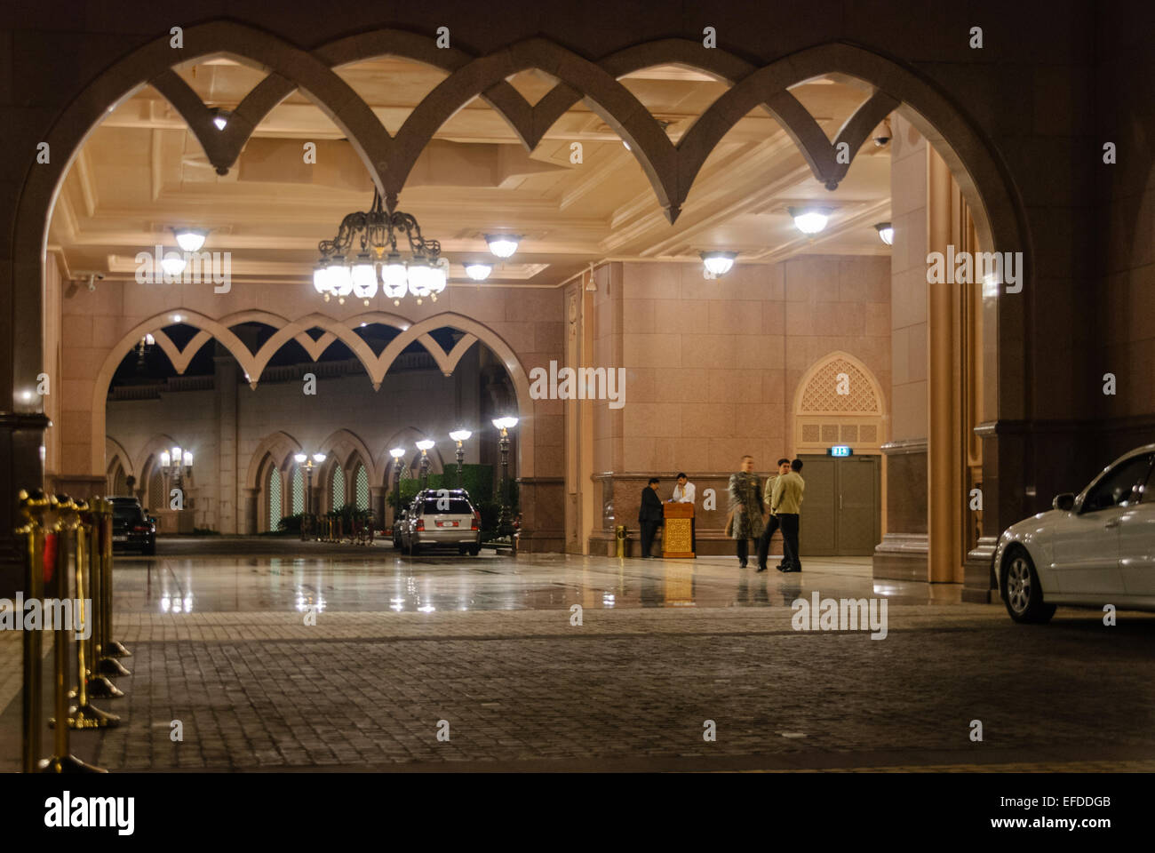 Front entrance to the Emirates Palace, Abu Dhabi, at night with concierge staff ready to greet guests - Stock Image