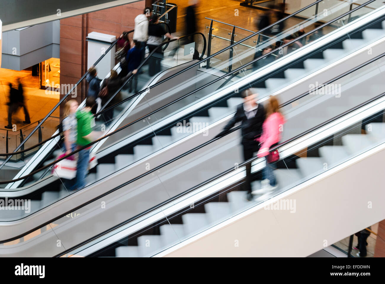 Shoppers Take The Escalators In A Shopping Centre/mall.   Stock Image