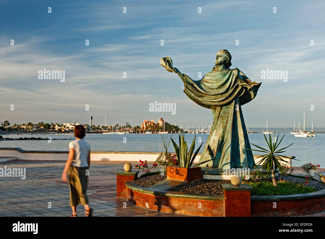 Woman walking by sculpture of person holding a shell and bay, Malecon (seaside promenade), La Paz, Baja California Stock Photo