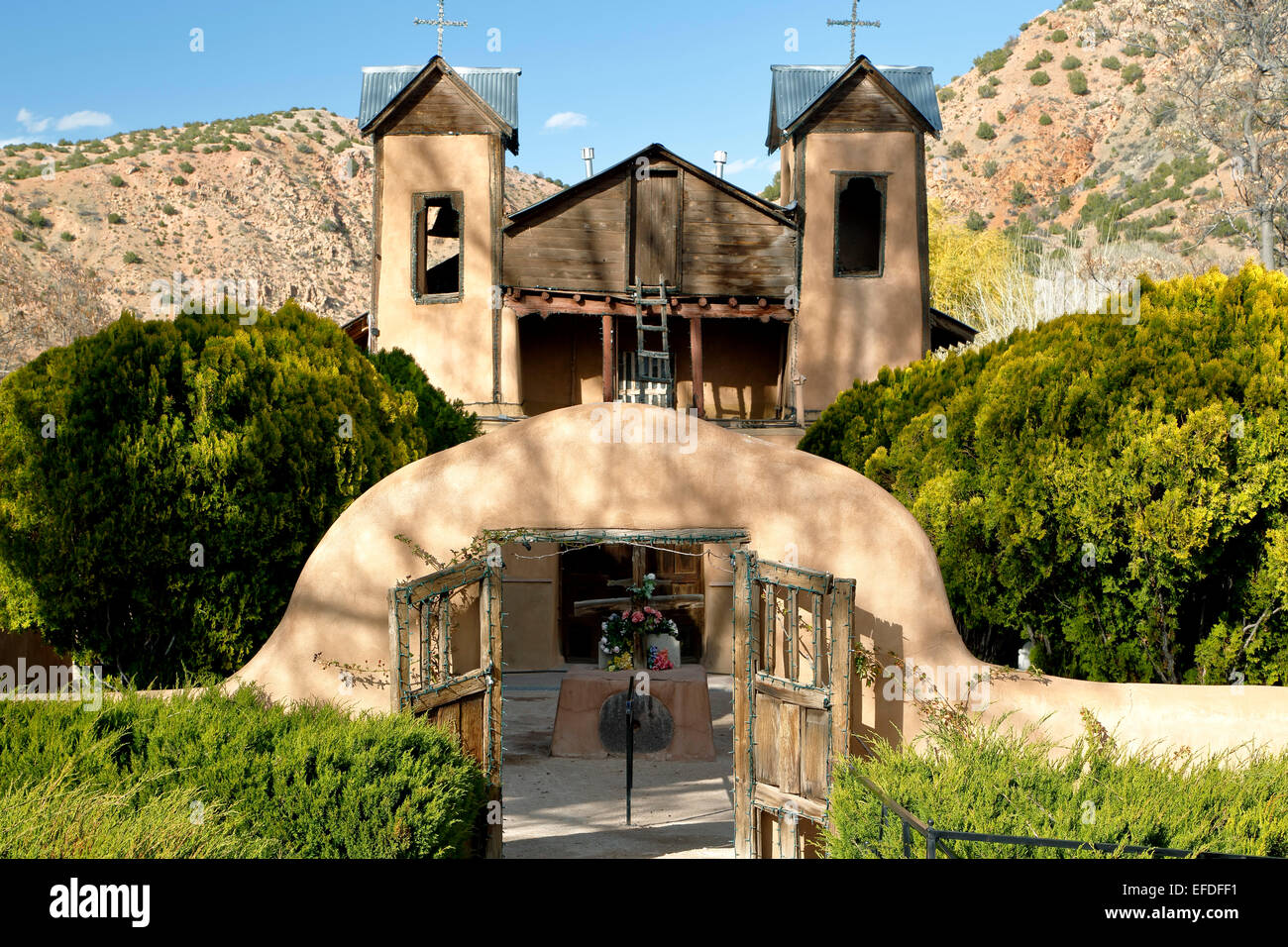 Adobe gate and Santuario de Chimayo, Chimayo, New Mexico USA - Stock Image