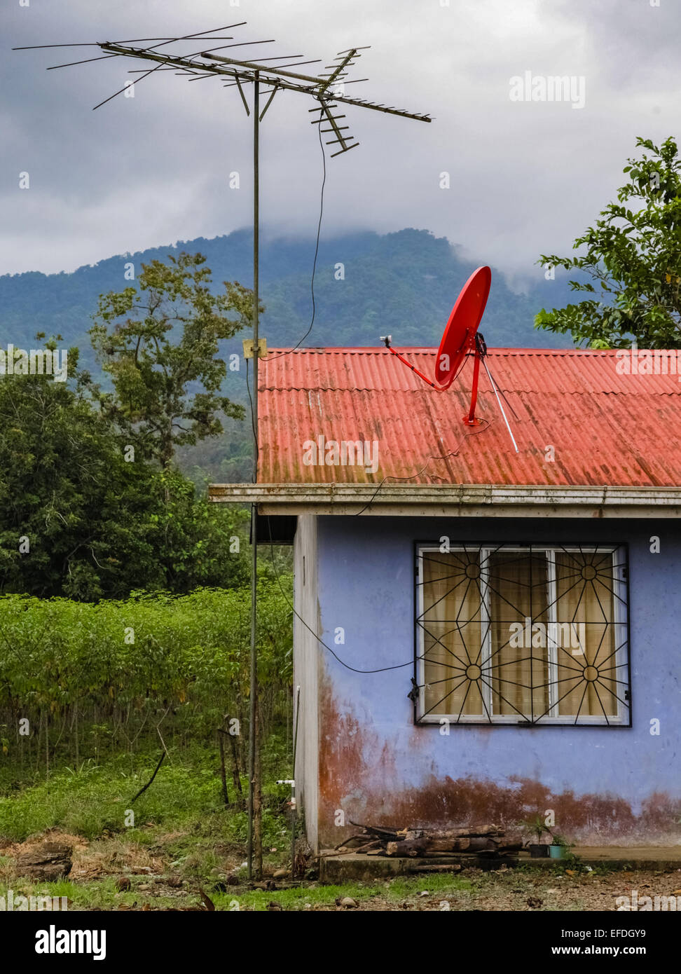 Telecommunication priorities of large aerial and satellite dish on the roof of a little house in Costa Rica - Stock Image
