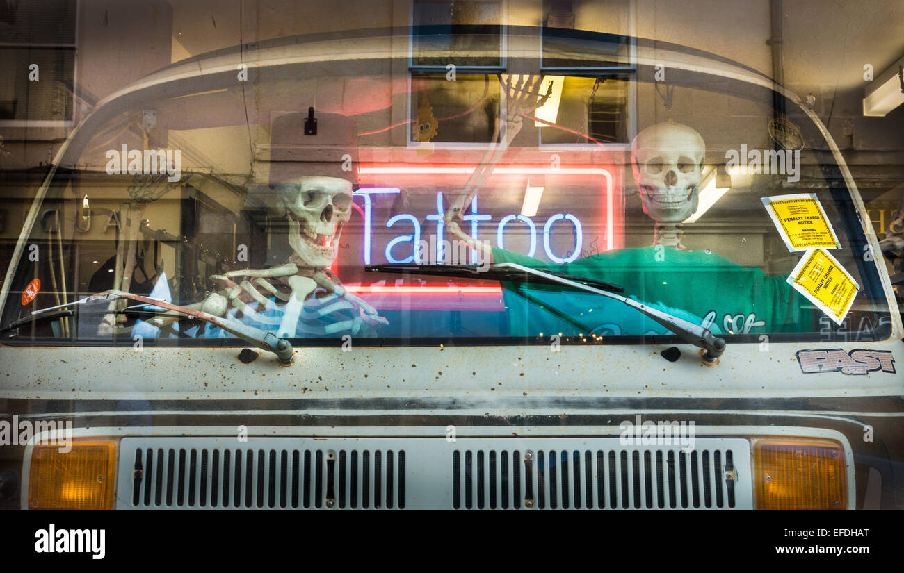 Amusing shop window display of a VW camper van with skeleton driver and companion in a Bath tattoo parlour Somerset - Stock Image