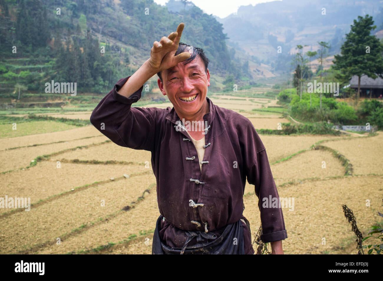 Portrait of Vietnamese Farmer in front of rice paddies, near Bac Ha, Vietnam, Asia - Stock Image