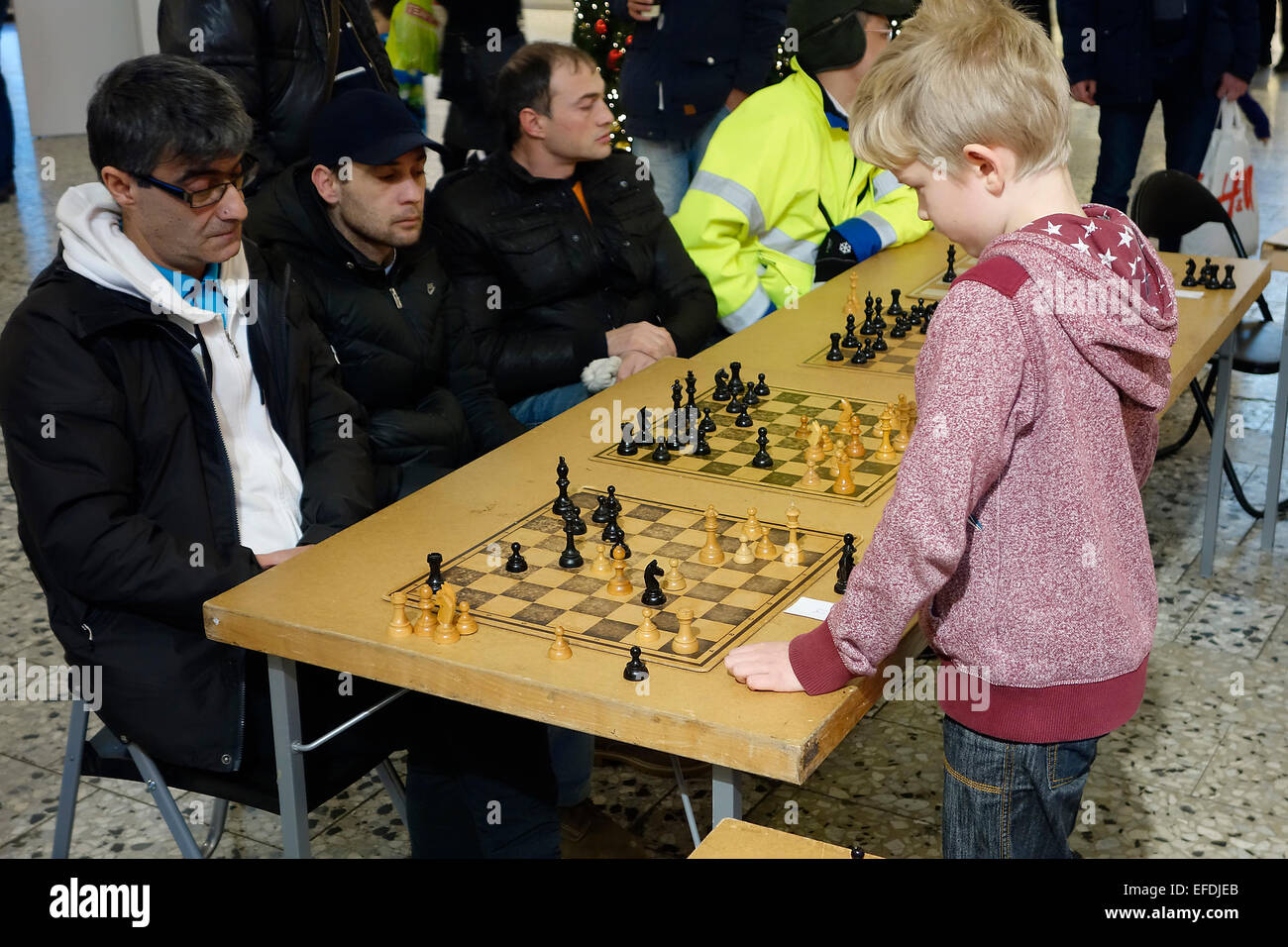 10 years old boy plays simultaneous chess game with 4 adult participants .  Nordstan, Göteborg,  Gothenburg, - Stock Image