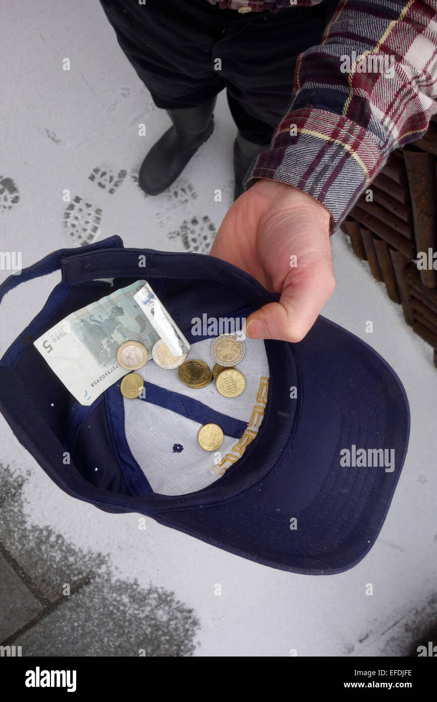 A man collecting euro notes and coins in his cap standing on a snow covered pavement. Stock Photo