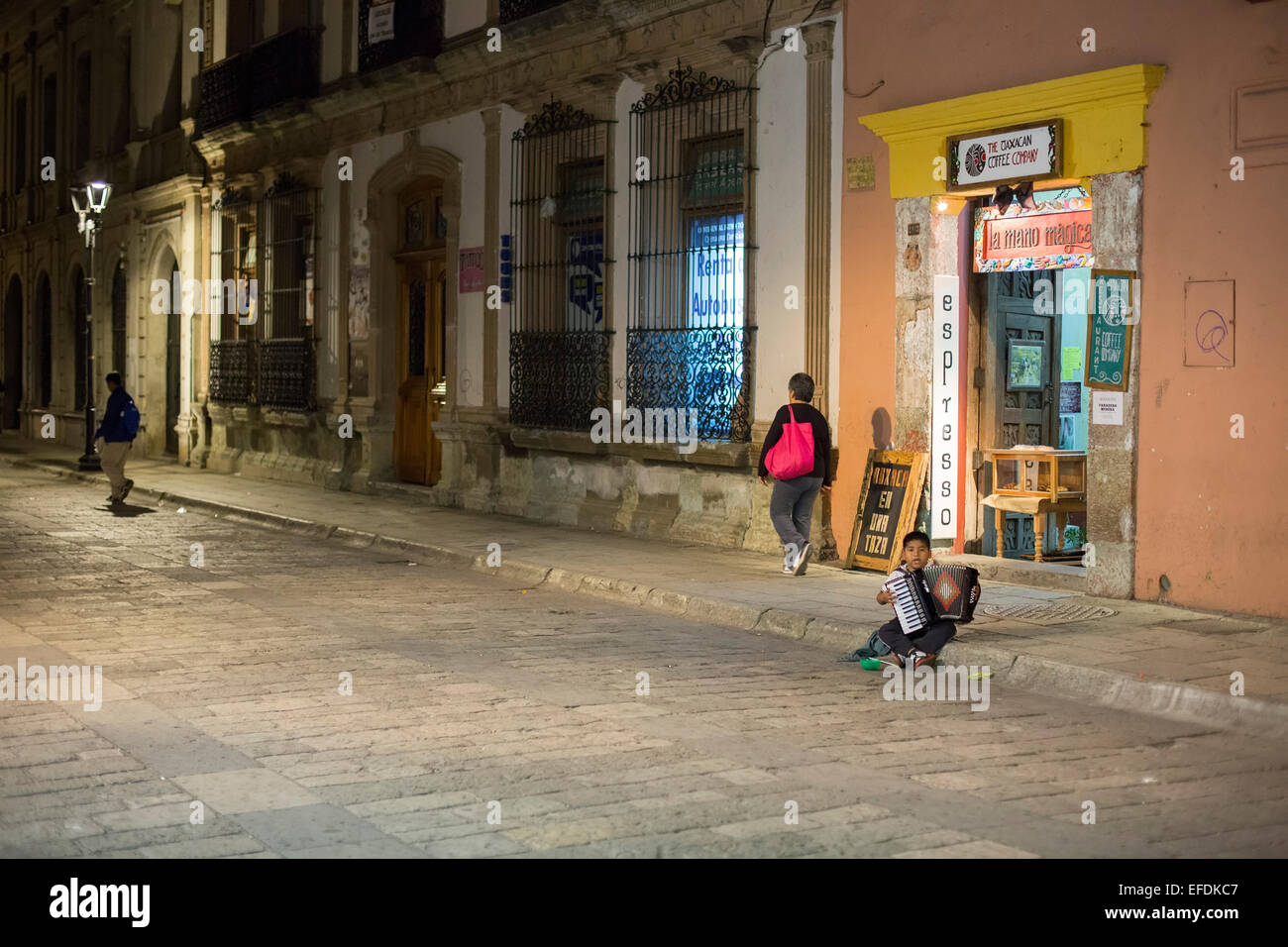 Oaxaca, Mexico - A seven-year-old boy plays the accordion and sings for tips on the street. - Stock Image
