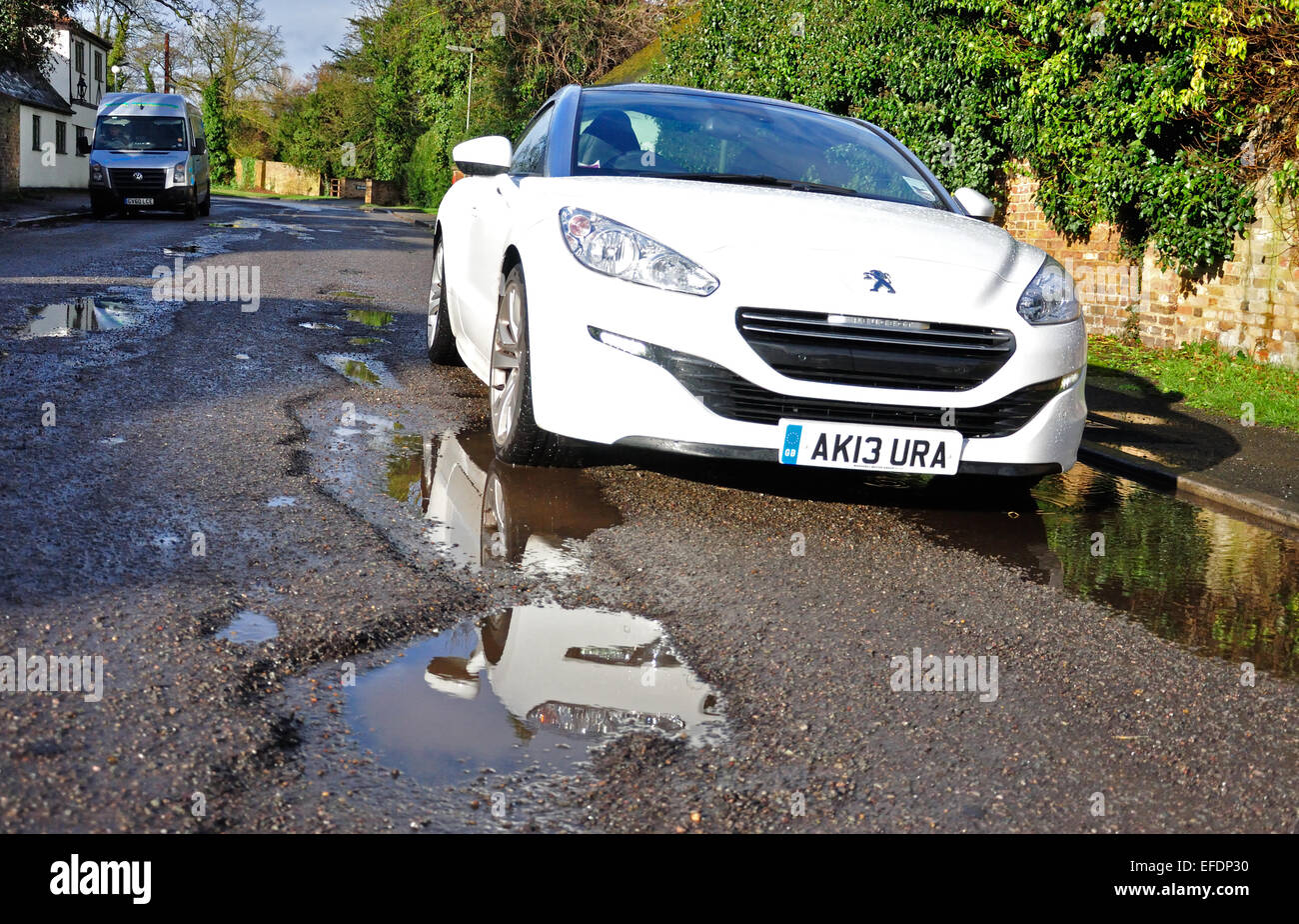 Wet potholes in road, Stanwell Moor, Surrey, England, United Kingdom - Stock Image