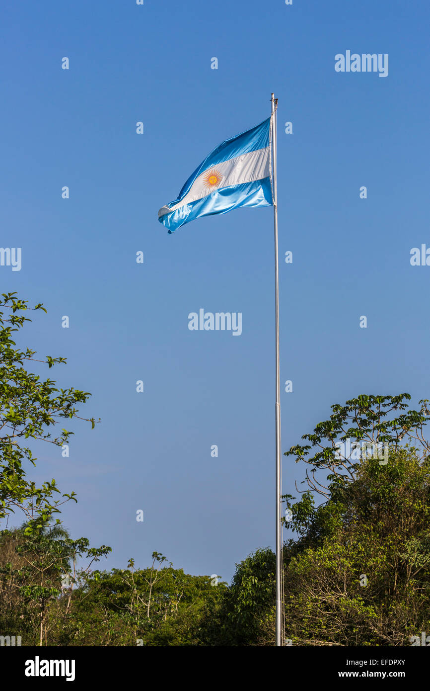 Blue and white Argentinian flag flying from a flagpole against a blue sky on a sunny day in Argentina - Stock Image