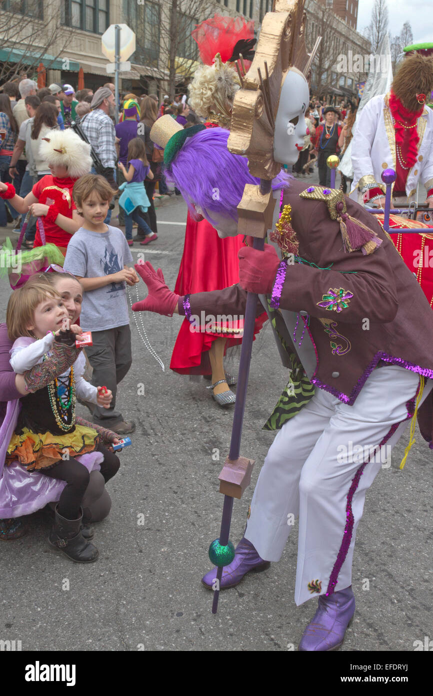 A colorful and personable clown greets children as he walks in the Asheville Mardi Gras parade - Stock Image