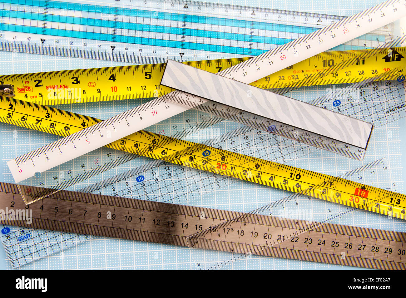 Rulers. Various types, transparent, plastic, metal, laid out on pale blue measuring grid board - Stock Image