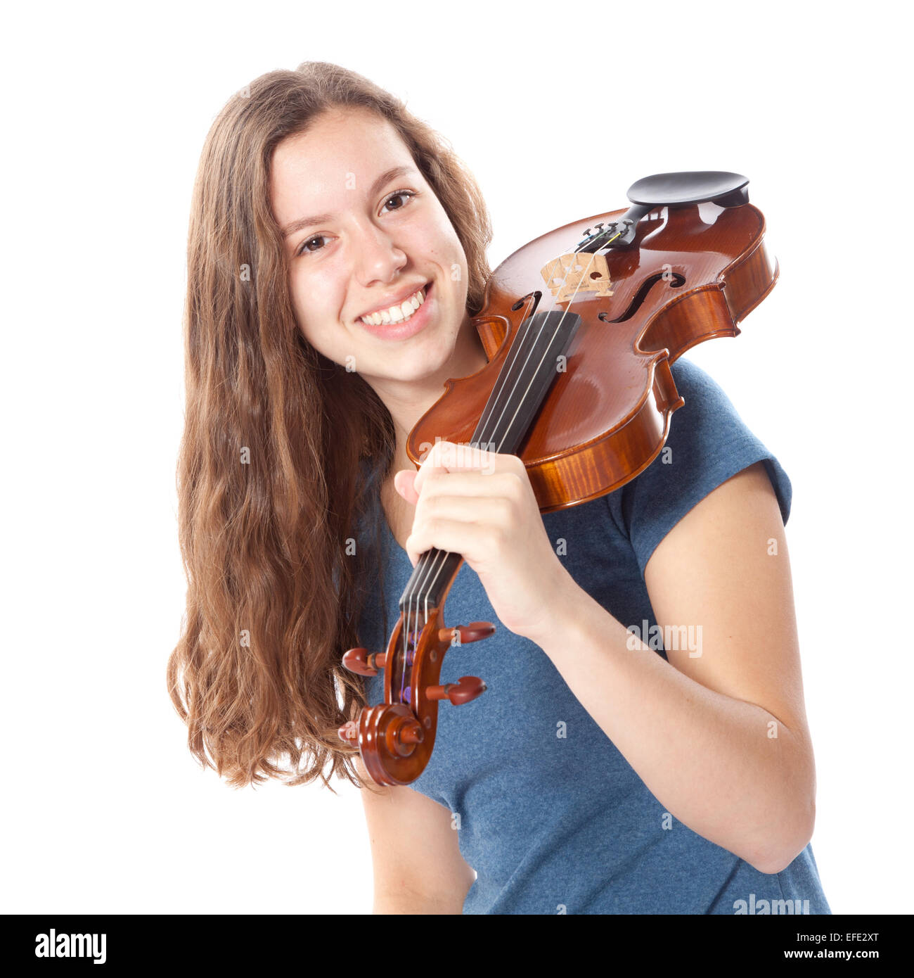 teen brunette  with violin on shoulder in studio against white background - Stock Image