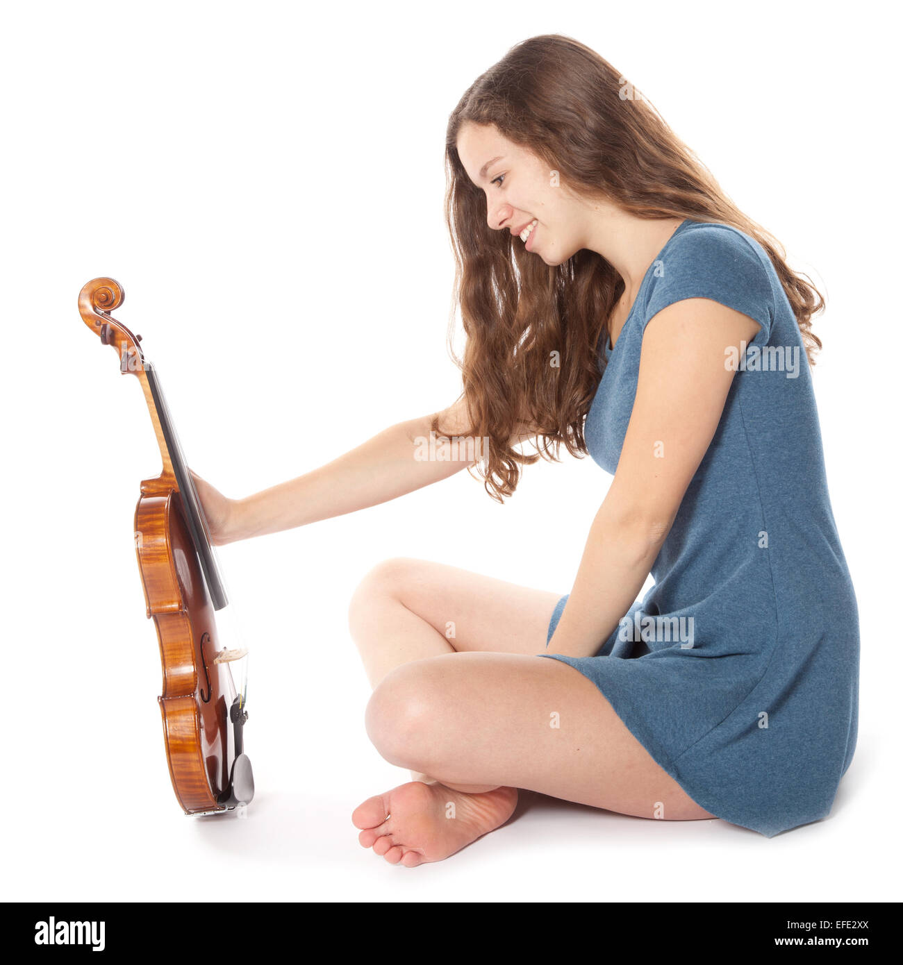 teen brunette wearing mini dress sits with violin in studio against white background - Stock Image