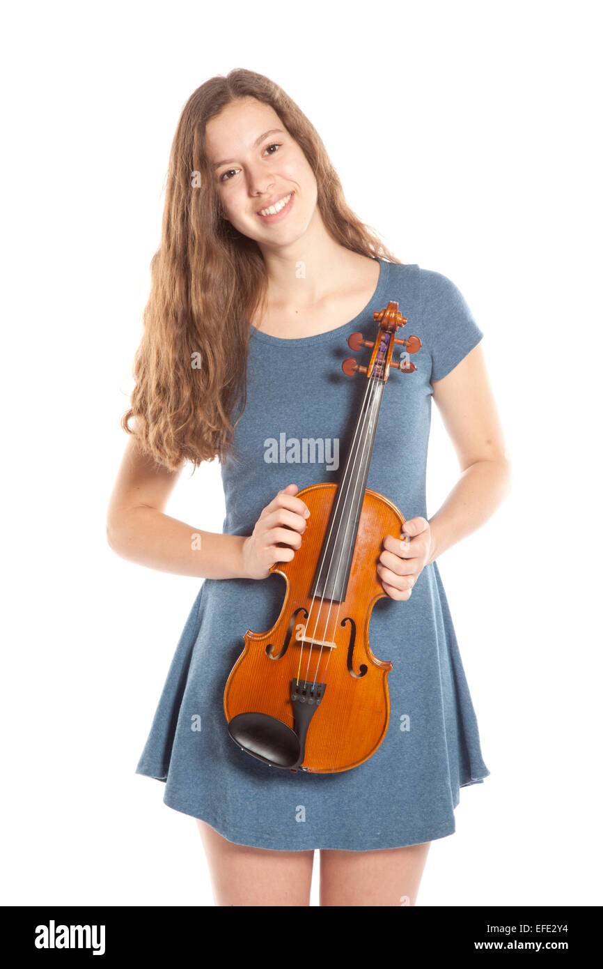 teen brunette in mini dress stands with violin in studio against white background - Stock Image