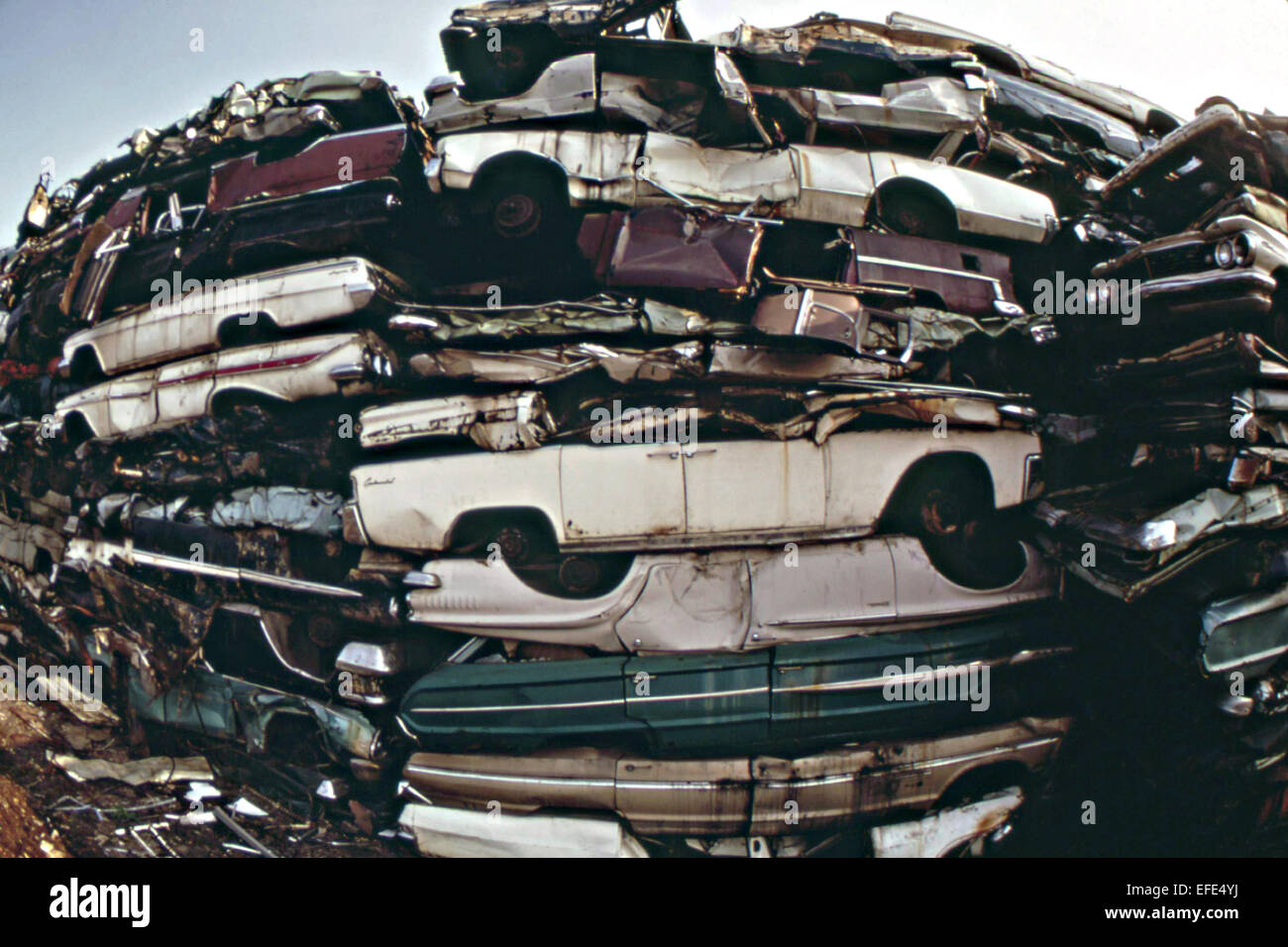 Junked automobiles stacked in a junkyard crushed for use as scrap metal August 1973 in Philadelphia, PA. - Stock Image