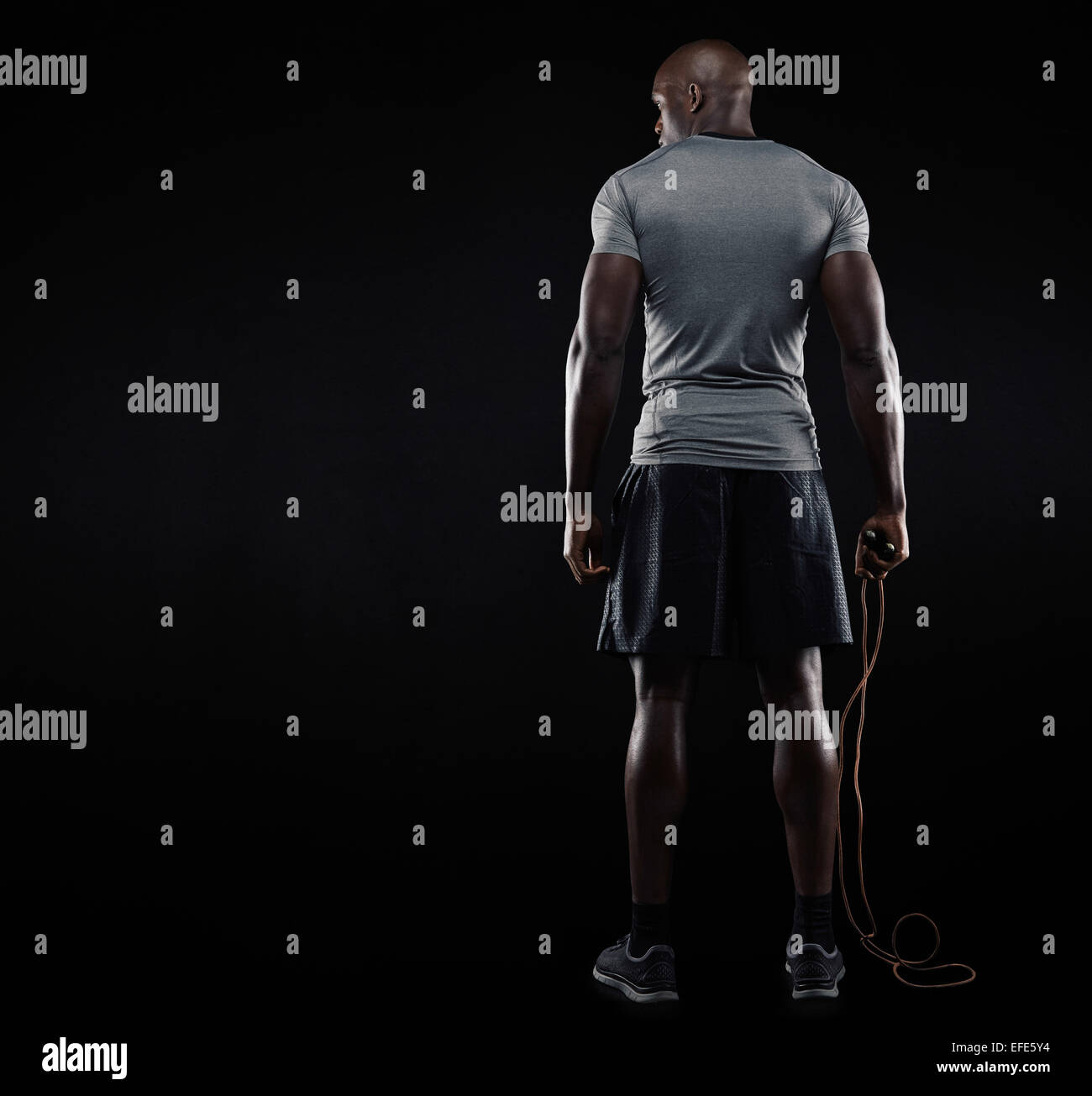 Rear view of muscular man standing with jumping rope on black background. Studio shot of fitness model holding skipping - Stock Image