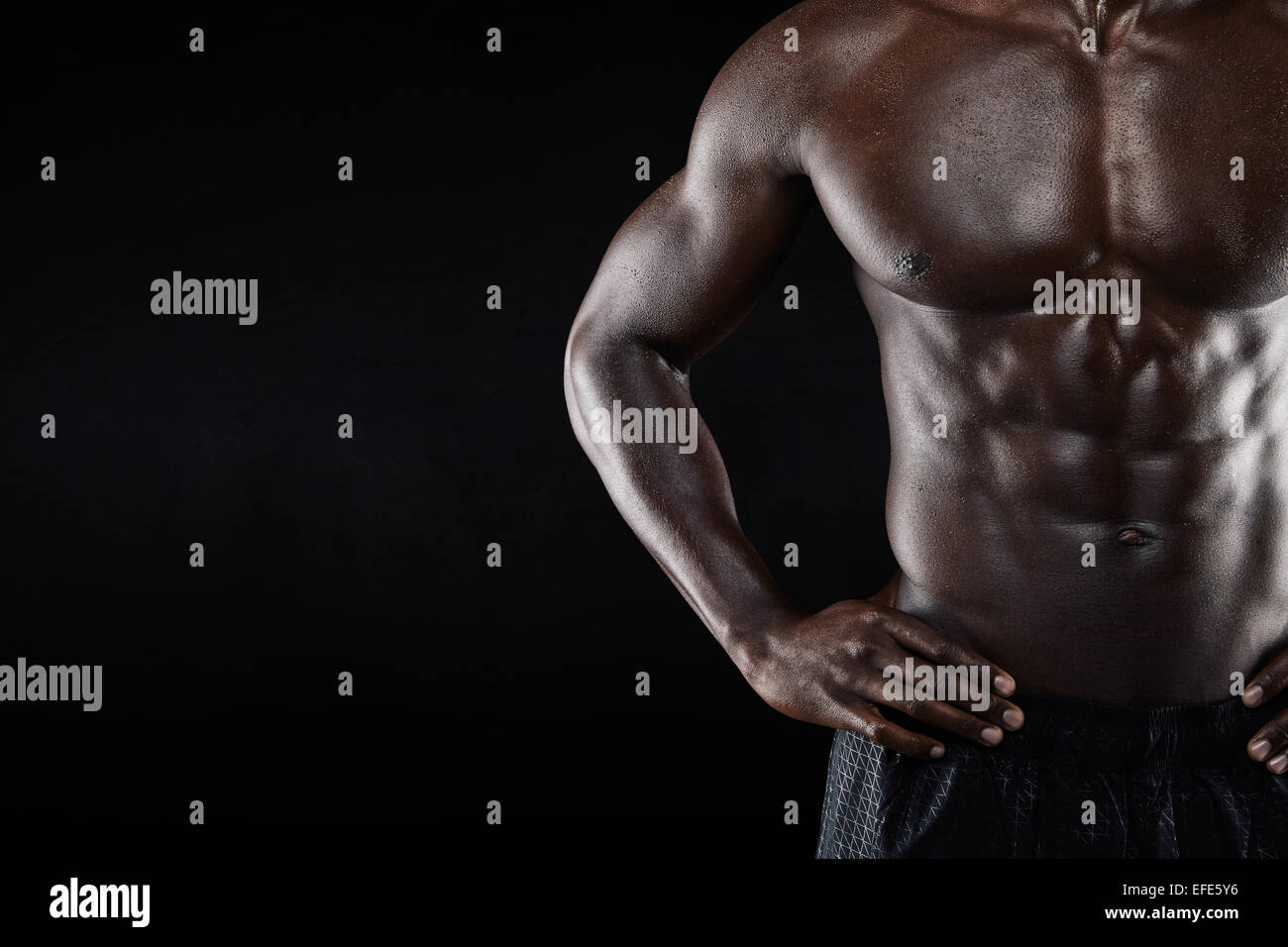 Close-up of shirtless african man with hands on hip while standing against black background. Cropped image of torso - Stock Image