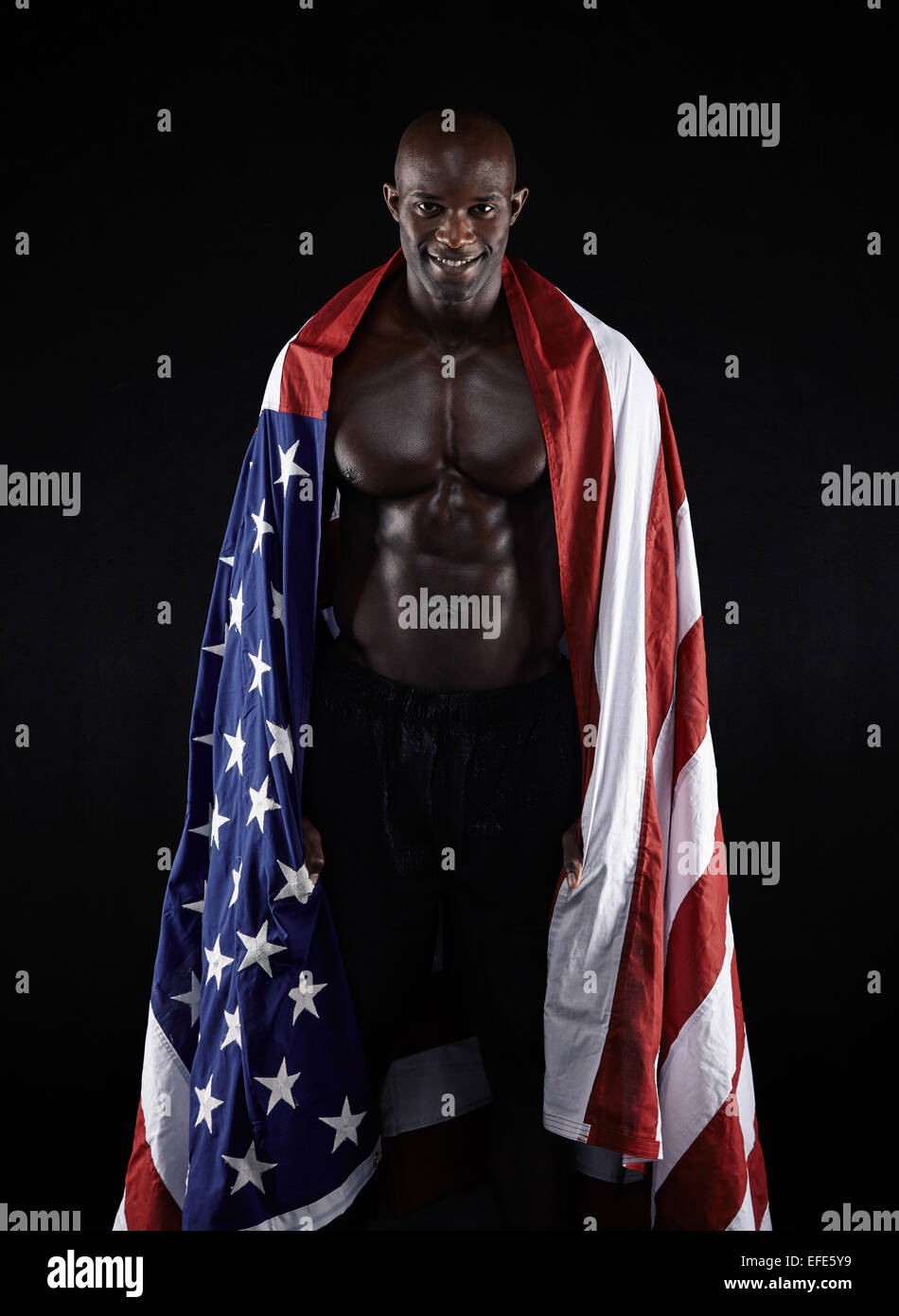 Young man wrapped in American flag against black background. Studio shot of muscular sportsman with USA flag looking - Stock Image