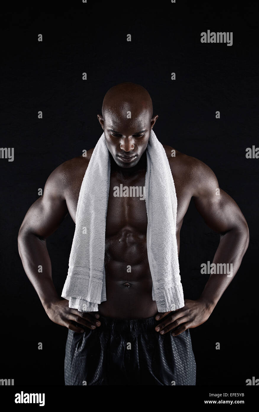 Shirtless muscular man with a towel looking down with his hands on hips on black background. Fit young african man - Stock Image