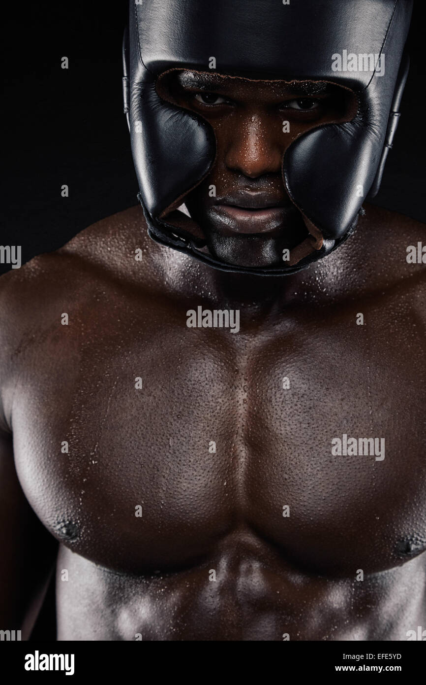 Closeup portrait of african boxer wearing protective head guard against black background. Muscular man wearing boxing - Stock Image