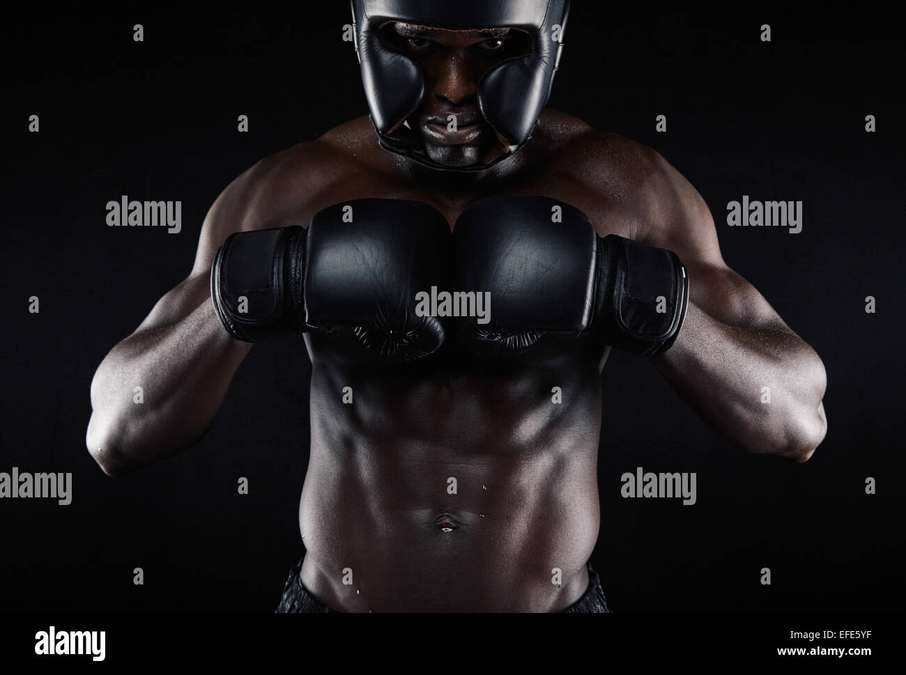 Portrait of young african male boxer preparing for competition against black background. Muscular male model wearing Stock Photo