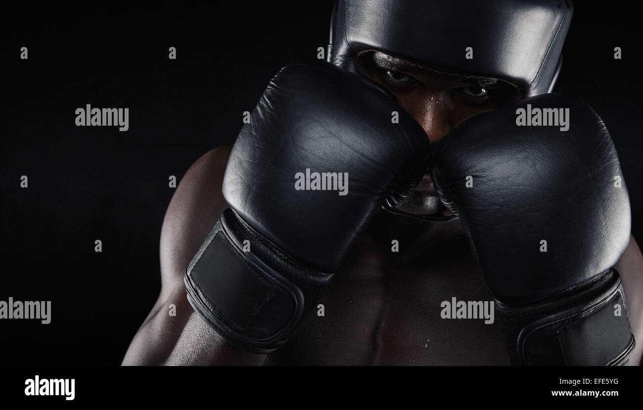African american boxer wearing protective gear against black background. Young man exercising boxing. - Stock Image