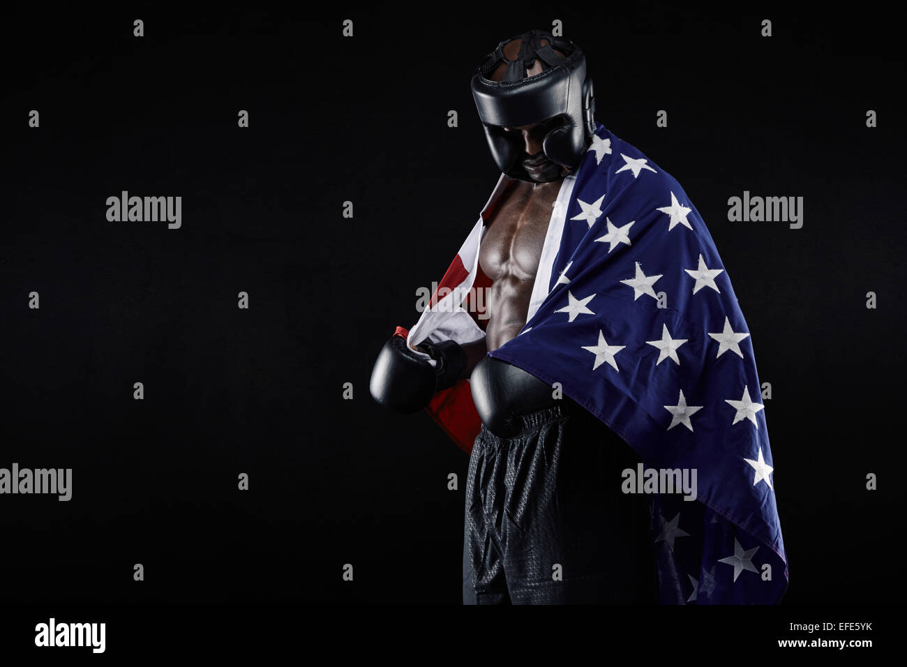 Portrait of young male boxer with American flag on black background. African man in boxing gear looking down. - Stock Image