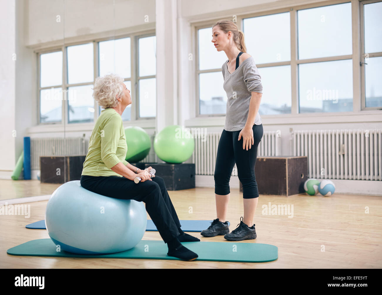 Physical therapist instructing a senior woman at rehab. Female trainer talking with old woman sitting on fitness Stock Photo