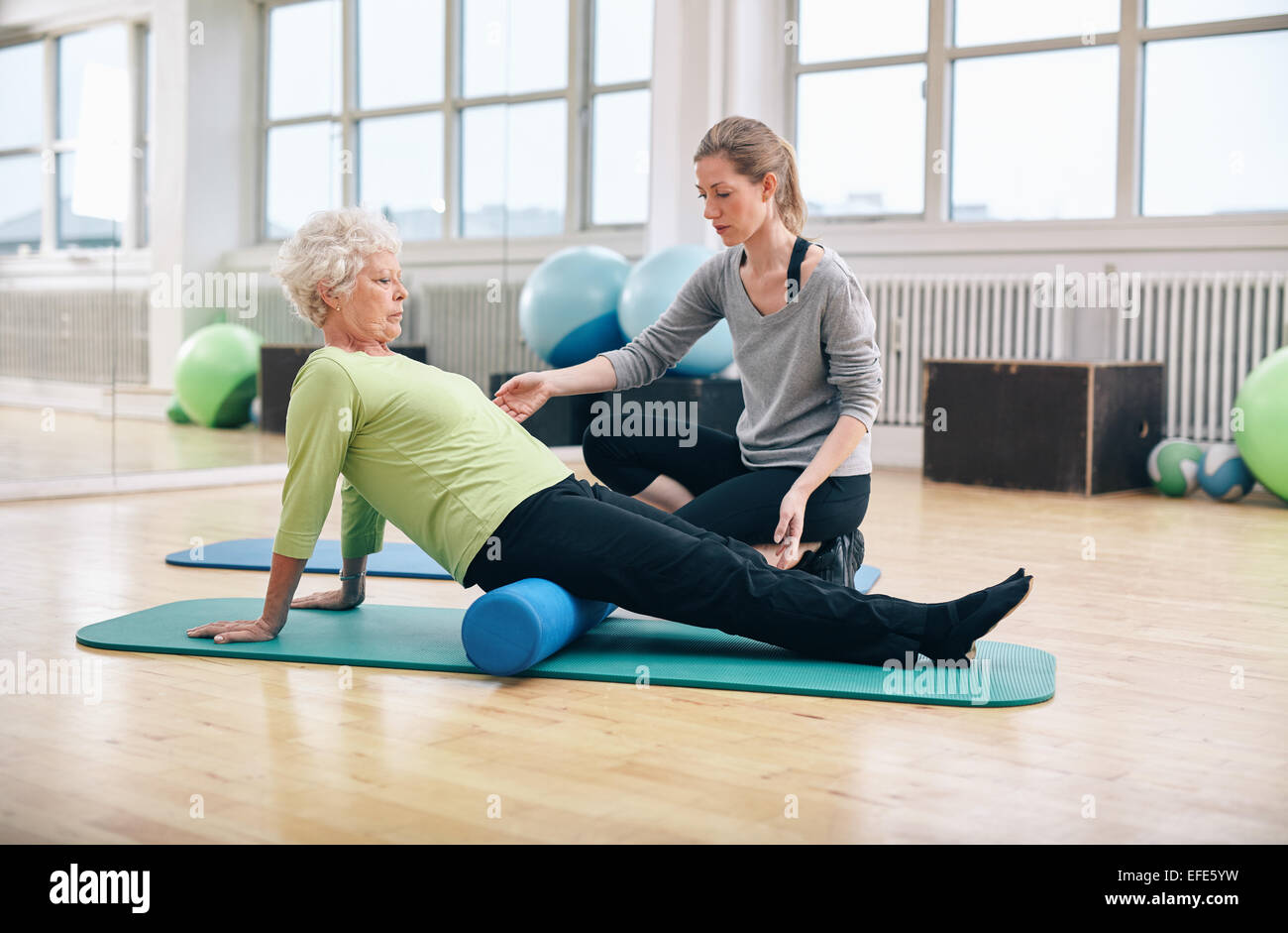Physical therapist working with active senior woman at rehab. Old woman exercising using foam roller with personal - Stock Image