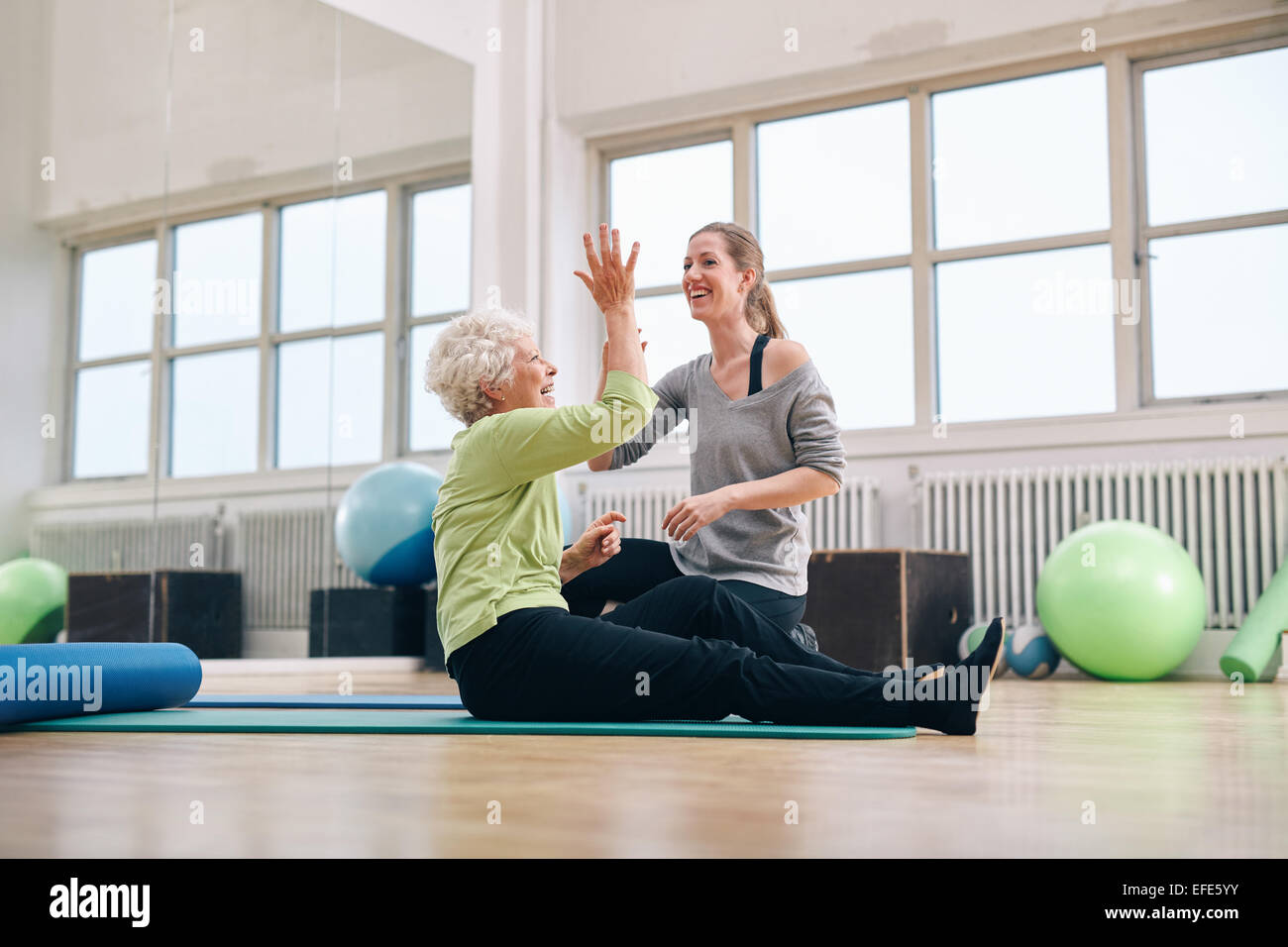 Senior woman giving high five to her personal trainer while sitting on fitness mat at gym. Happy elder woman rejoicing - Stock Image