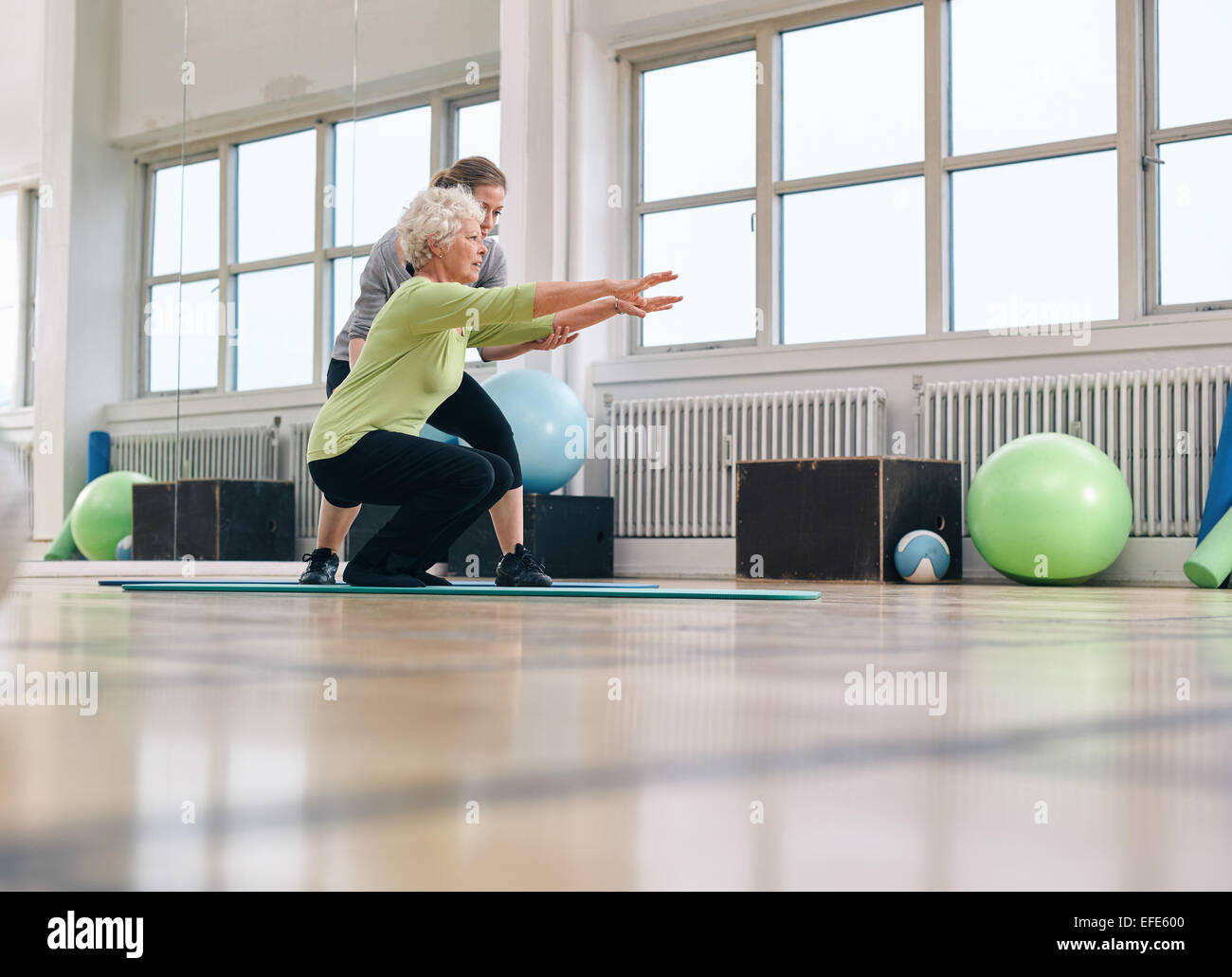 Senior woman doing exercise with her personal trainer at gym. Gym instructor assisting elder woman in her workout. - Stock Image