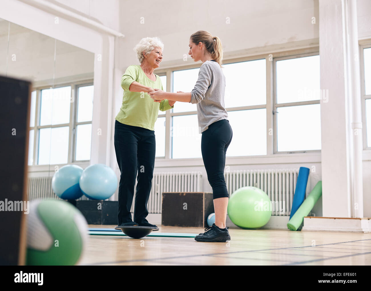 Female trainer helping senior woman in a gym exercising with a bosu balance training platform. Elder woman being - Stock Image