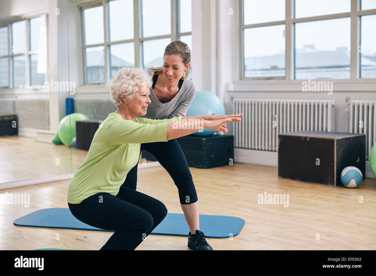 Elderly woman doing exercise with her personal trainer at gym. Gym instructor assisting senior woman in her workout. - Stock Image
