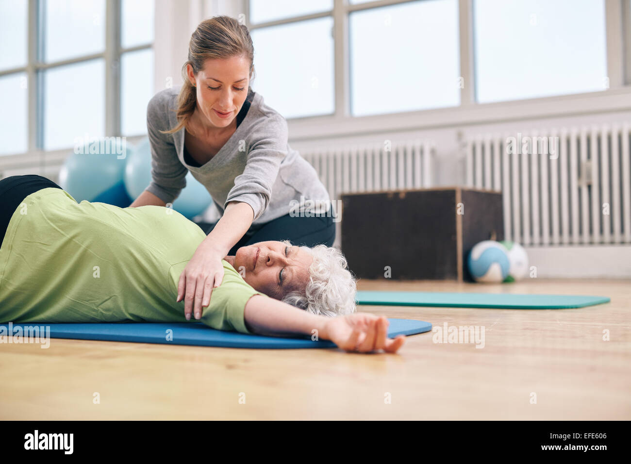 Senior women lying on exercise mat doing stretching workout for back muscles with coach assistance. Female trainer - Stock Image
