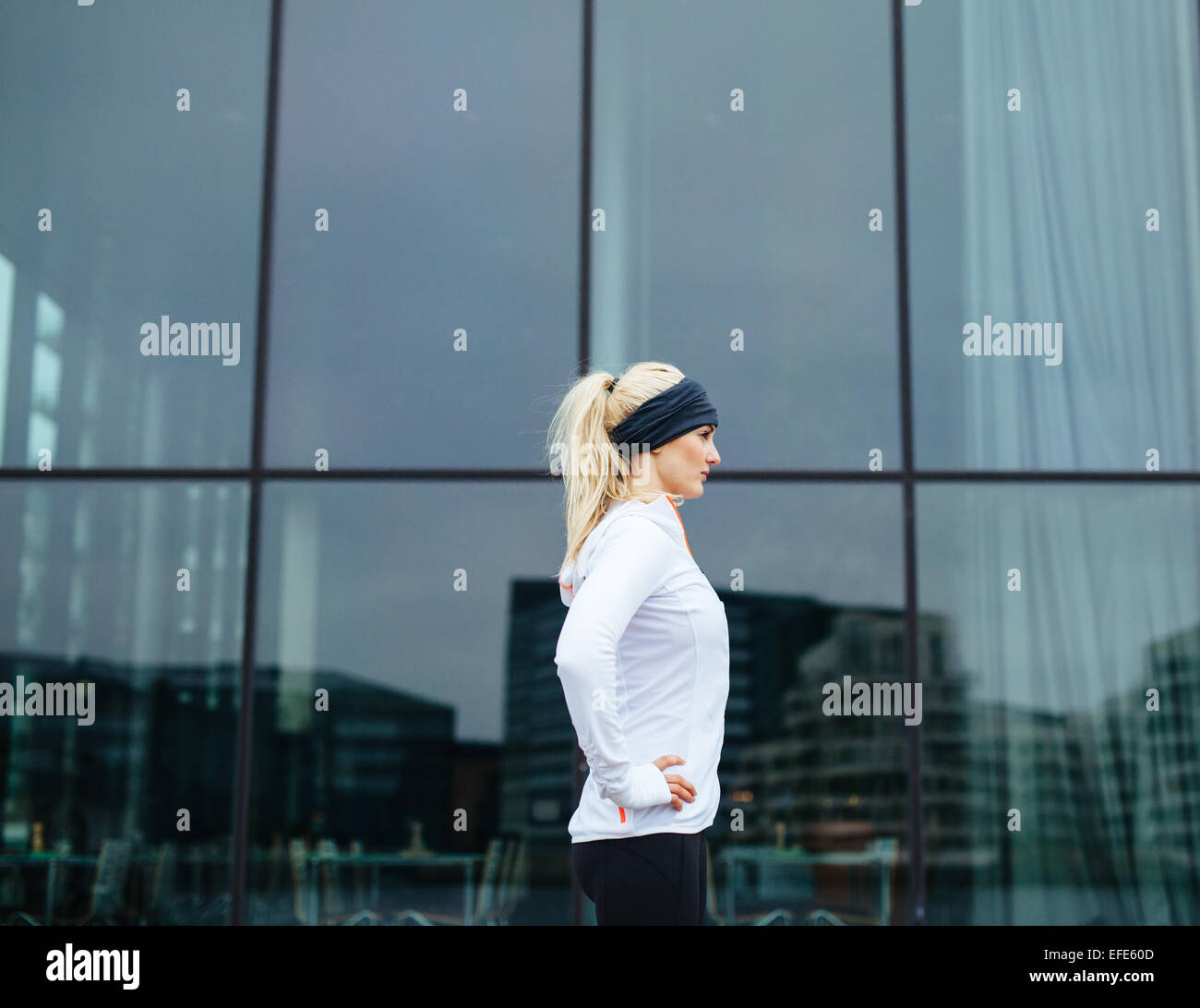 Side view of an sporty young female ready for her outdoor training session. Fitness woman standing outdoors with - Stock Image