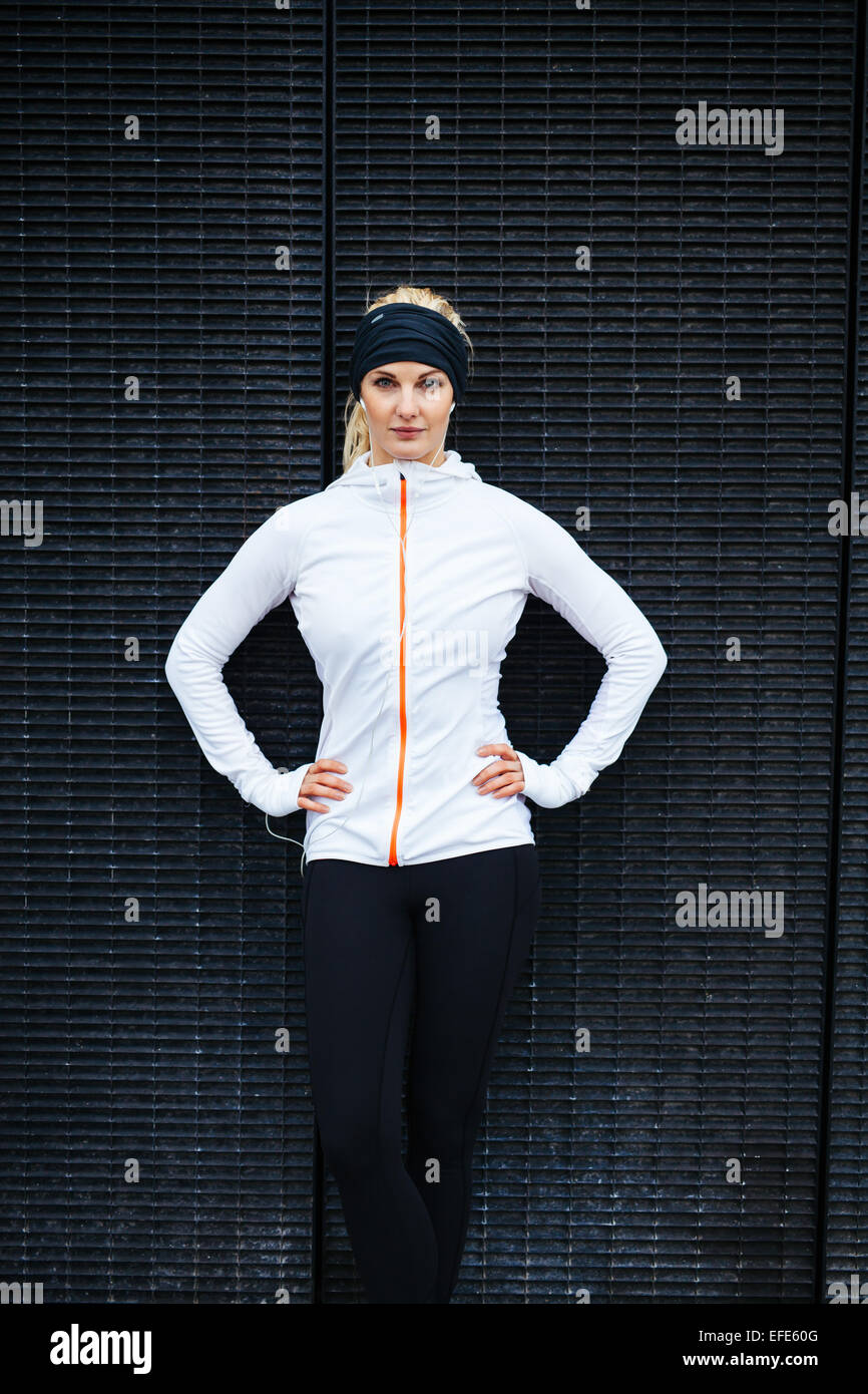 Sporty young woman standing confidently with her hands on hips against a wall. Positive female athlete outdoors. - Stock Image