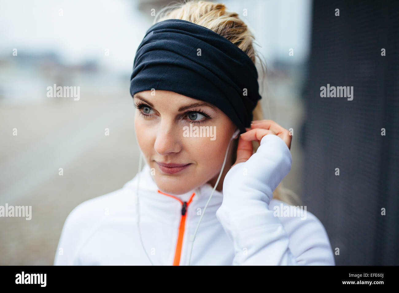 Close-up portrait of beautiful sportswoman wearing headband and listening to music on earphones. Fitness female - Stock Image