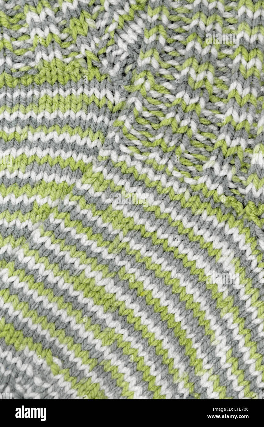 close up of two green, gray and white flecked and striped knitted wool socks, full frame, vertical - Stock Image