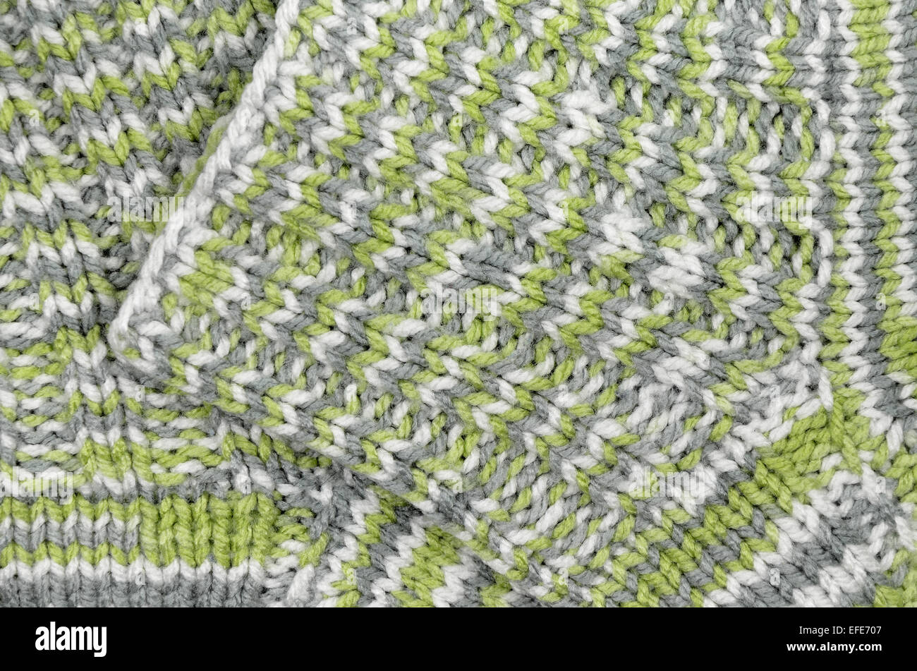 close up of two green, gray and white flecked and striped knitted wool socks, full frame - Stock Image