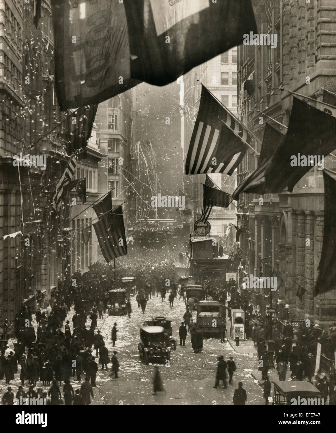 Germany Surrenders - celebrations on Wall Street with confetti, American flags, and crowds of people. November 1918 - Stock Image