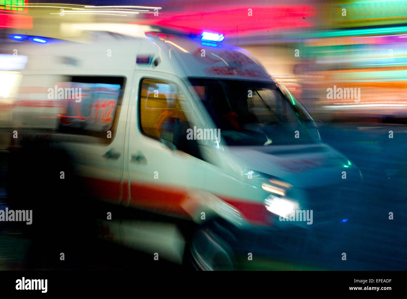 An ambulance speeds through the streets of Istanbul at night time - Stock Image