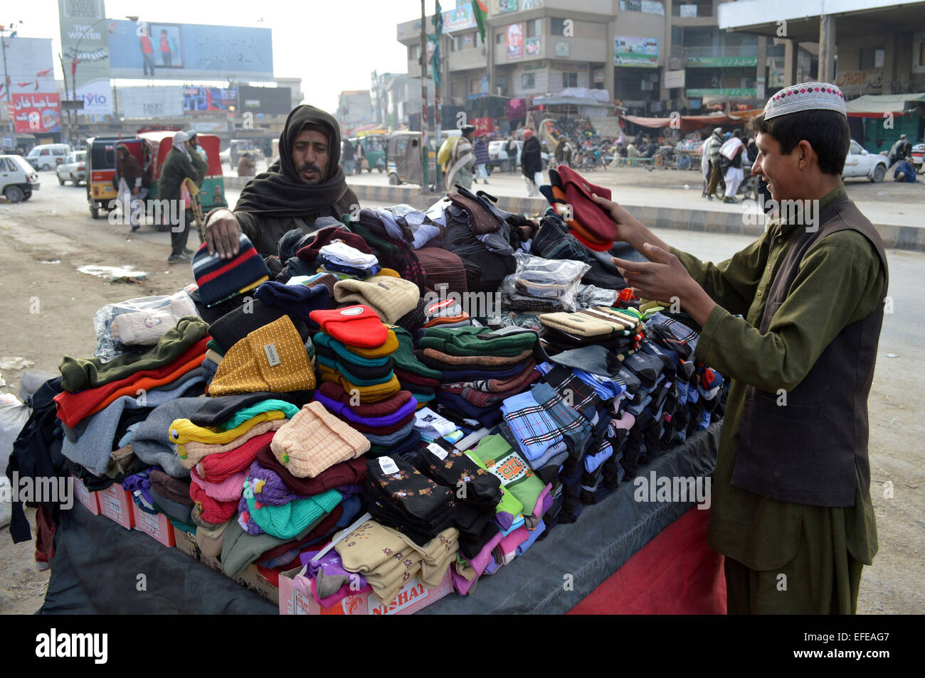 Quetta. 2nd Feb, 2015. A vendor sells beanies to a customer in southwest Pakistan's Quetta, Feb. 2, 2015. © - Stock Image
