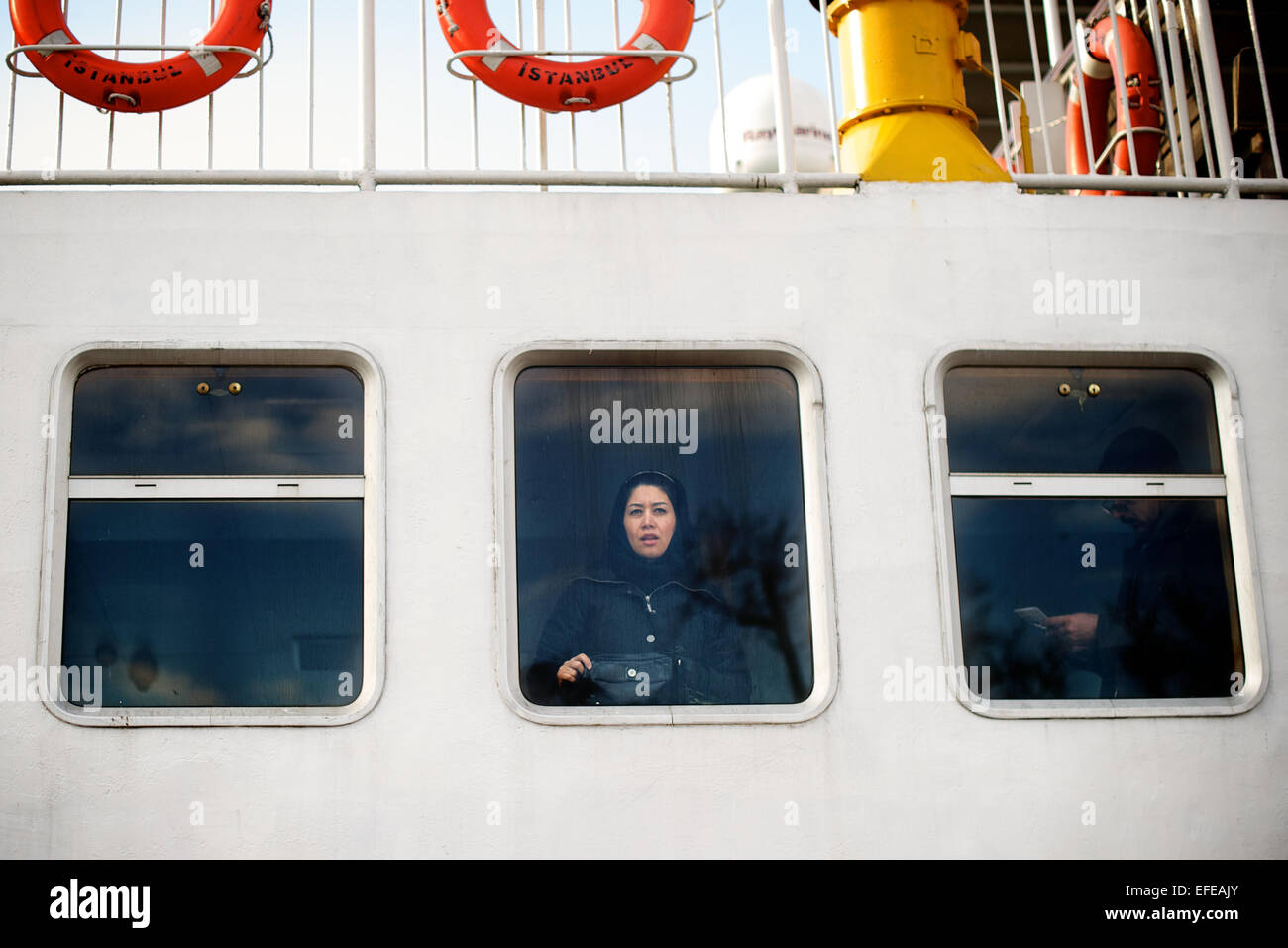 A woman peers out at the view on a bosphorous ferry is pictured as part of a photo essay on winter breaks in Istanbul, Stock Photo