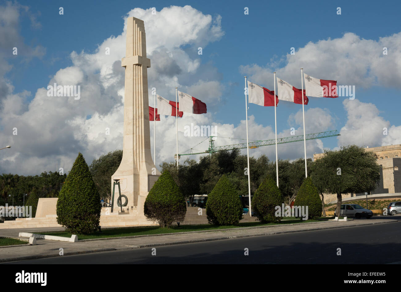 Maltese flags fly proudly in the wind by the war memorial in Floriana just outside the walls of Valletta - Stock Image