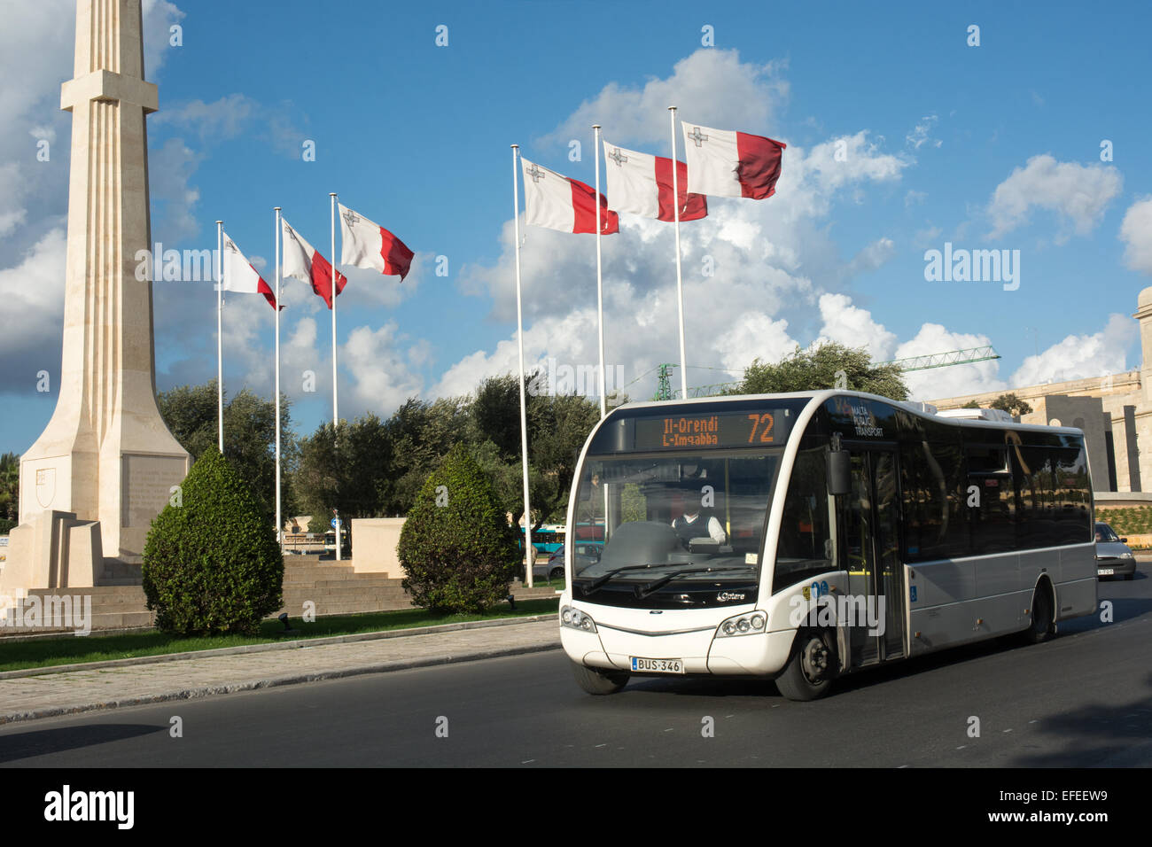 A Malta Public Transport Optare Solo SR low floor bus has just left Valletta bus station and passes the war memorial - Stock Image