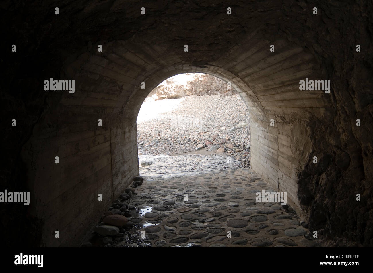 tunnel tunnels secret private beach beaches stone stony out of the darkness into the light emerging escape Stock Photo
