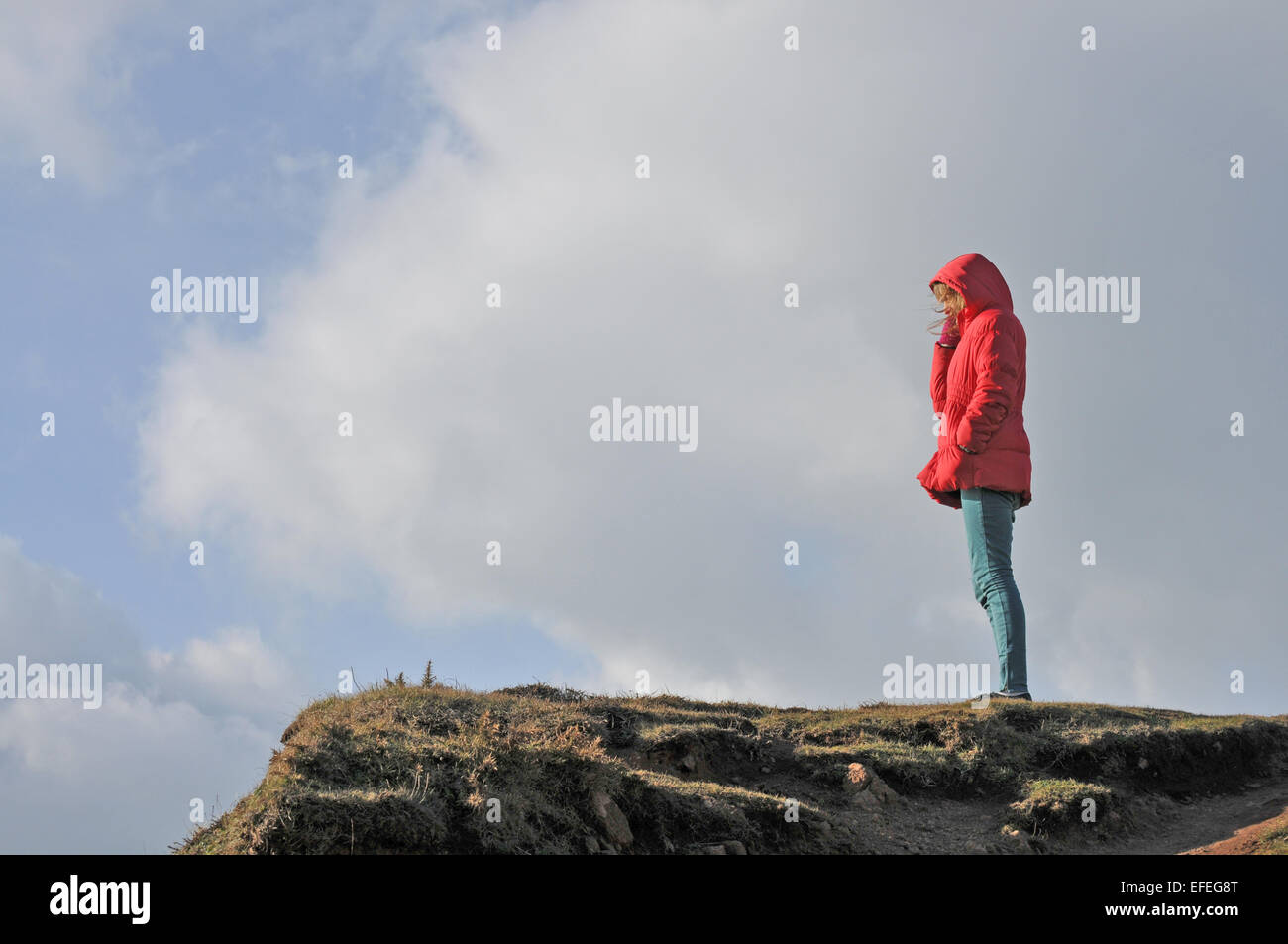 A 12 year old girl looks out over the sea at Kynance Cove, Cornwall - Stock Image