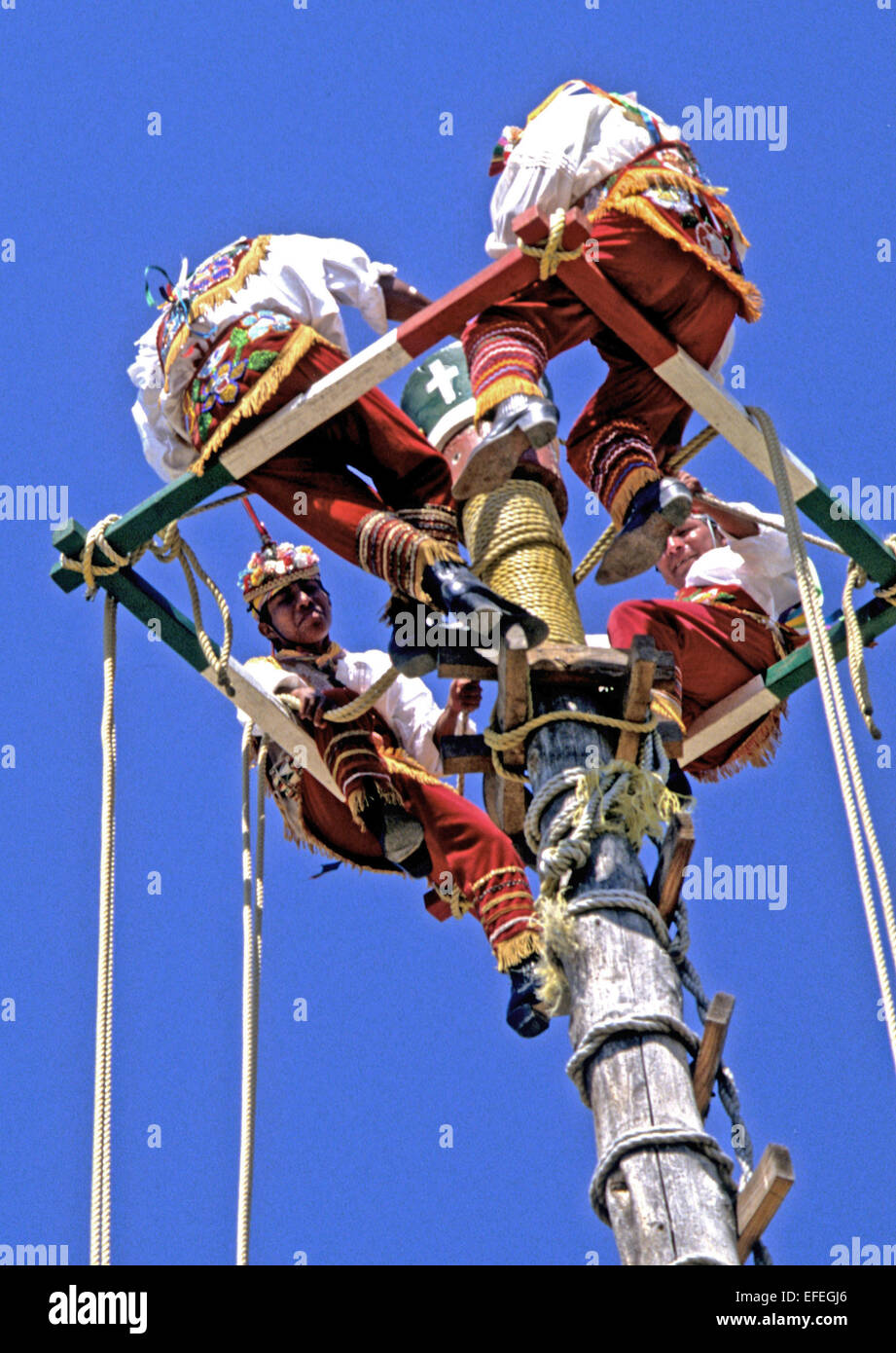 Mexico - Totonac Indians perform intricate weaving dance routines on top of a pole nearly 100 feet up in the air. - Stock Image